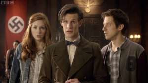 The Doctor, flanked by Amy and Rory, stands in front of a swastika flag