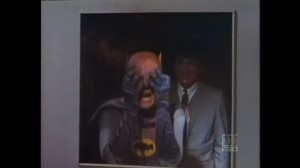 Batman screams, reflected in the glass, as False-Face looks on