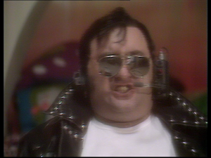 Alexei Sayle as a stereotypical 1950s greaser, with leather jacket and sunglasses
