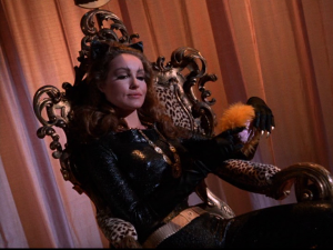Catwoman sits on a leopardskin throne