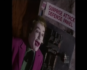 "The Joker in front of a ""Surprise Attack Defense Panel"""